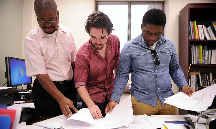 From left, cold case researchers Wilborn Nobles III, Gordon Brillon and Joshua Jackson review materials to build the program's interactive website.