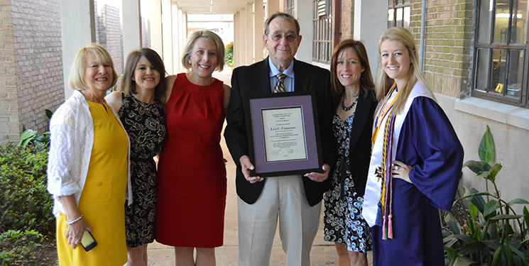 Leo Comeaux's daughters present him with the Leo C. Comeaux Chemical Engineering Scholarship at his granddaughter's graduation from the College of Engineering.